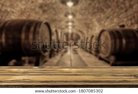 Empty wooden table in front of a wooden wine barrels in wine cellar. Concept Product Banner  Сток-фото ©
