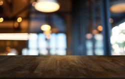 Empty wooden table in front of abstract blurred background of coffee shop . wood table in front can be used for display or montage your products.Mock up for display of product