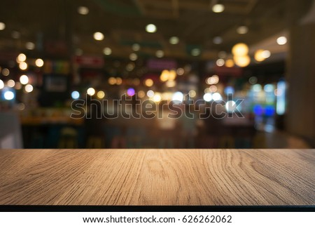 Empty wooden table in front of abstract blurred background of sh #626262062