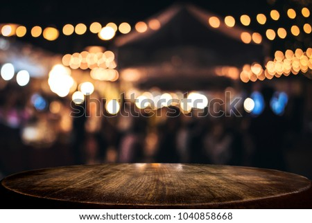 Empty wooden table in front of abstract blurred festive background with light spots and bokeh for product montage display of product.