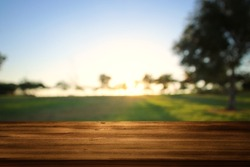 Empty wooden table in front of dreamy countryside sunset background. product display and picnic concept