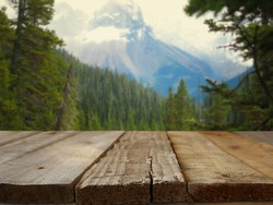 Empty wooden table in front of fir forest and snowy mountains landscape background. For product display montage
