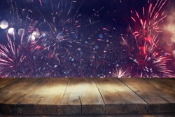 Empty wooden table in front of fireworks background. Product display montage