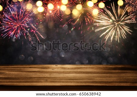 Empty wooden table in front of fireworks background. Product display montage #650638942