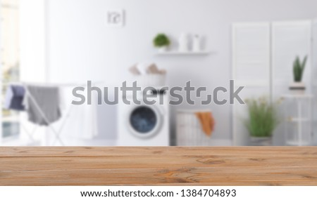 Empty wooden table in laundry room. Mockup for design  #1384704893