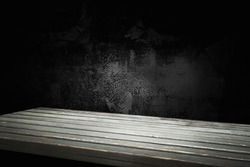 empty wooden table on background of empty dark cracked wall, with focal light