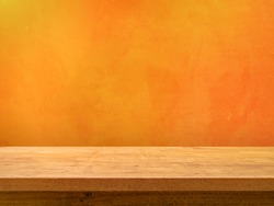 Empty wooden table on orange textured wall