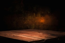 empty wooden table on the background of an empty dark wall, with focal light, for the montage of your project