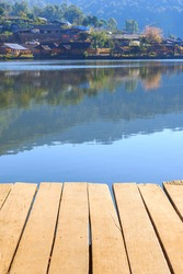 Empty wooden table or plank with lake and village on the mountain background for product display. in vertical alignment.