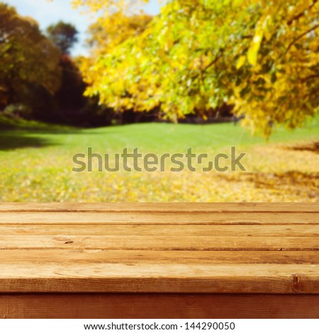 Empty wooden table over autumn park background. Ready for product montage