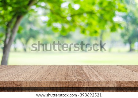 Empty wooden table over blurred tree with bokeh background, for product display montage