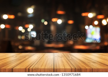 Empty wooden table top with blurred coffee shop or restaurant interior background. Abstract background can be used for display or montage your products.  #1350971684