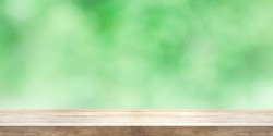 Empty wooden table top with blurred green natural abstract background. Panoramic banner. Can be used product display.