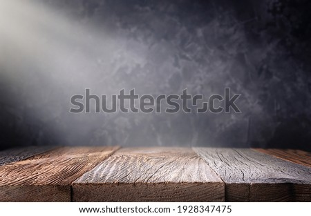 Empty wooden table top with defocused dark concrete wall background. Template for product display