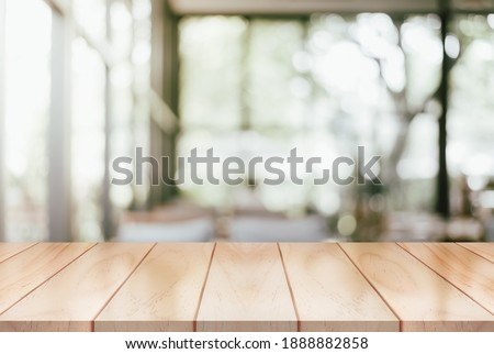 Empty wooden table top with lights bokeh on blur restaurant background.