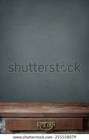 empty wooden table with a box against a blue wall