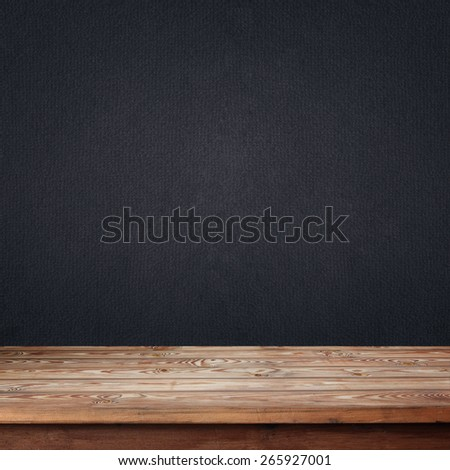 empty wooden table with a box against a dark wall