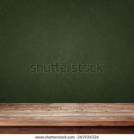 empty wooden table with a box against a green wall