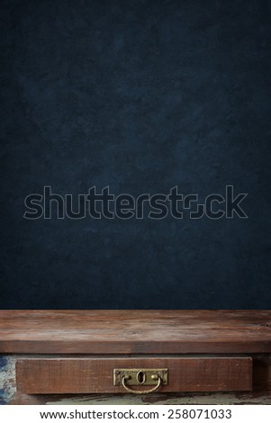 empty wooden table with a box against a wall