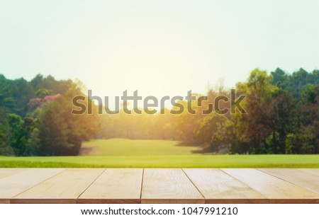 Empty wooden table with blurred green natural abstract background. #1047991210