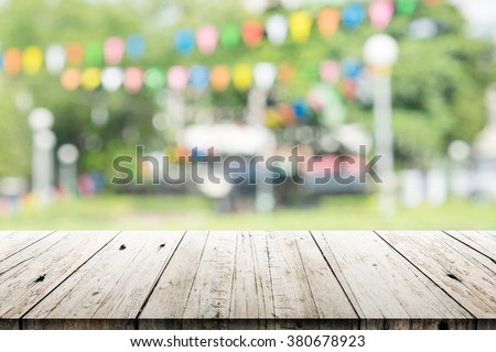 Empty wooden table with blurred party on background,  fun / spring concept #380678923