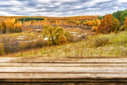 Empty wooden table with blurred picturesque autumn landscape of view from the hill to the lowland with forest and swamps. Can be used for display or montage products