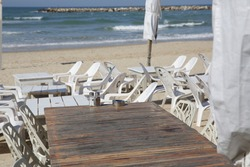 empty wooden table with chairs and deck chairs and umbrellas on a background of blue sea. Restaurant by the sea or ocean. Nobody. With copy space for text