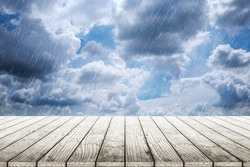 Empty wooden table with clouds and rain background blurred.
