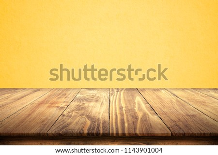 Empty wooden table with concrete wall of light yellow color, texture turquoise cement background, of free space for your copy and branding. Use as products display montage. Vintage style concept. #1143901004