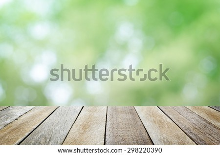 Empty Wooden Table with Fresh Foliage Abstract Circle Bokeh Background for Product or Object Montage Display