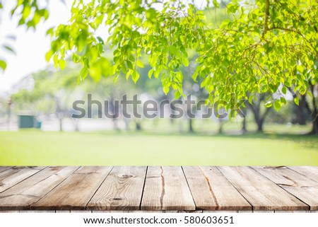 Empty wooden table with garden bokeh for a catering or food background with a country outdoor theme,Template mock up for display of product #580603651