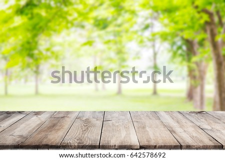 Empty wooden table with garden bokeh for a catering or food background with a country outdoor theme,Template mock up for display of product #642578692