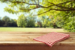 Empty wooden table with tablecloth over autumn nature park background