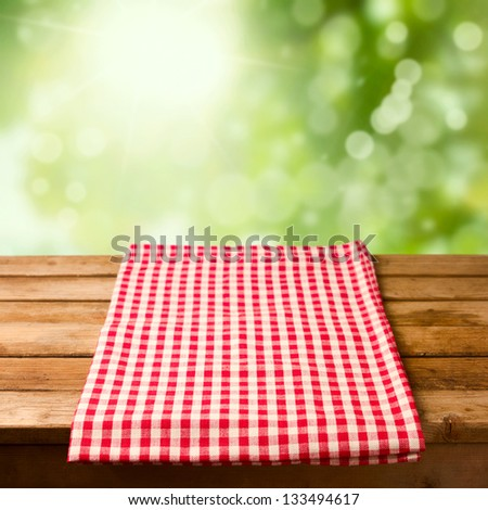Empty wooden table with tablecloth over bokeh background