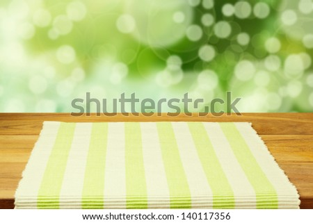 Empty wooden table with tablecloth over bokeh background. Ready for product montage