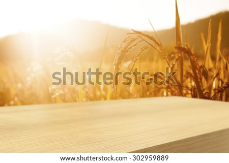 Empty  wooden table with wheat field background, product display montage