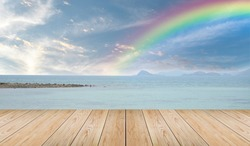 Empty wooden tabletop and view tropical beach with raibow over sea background
