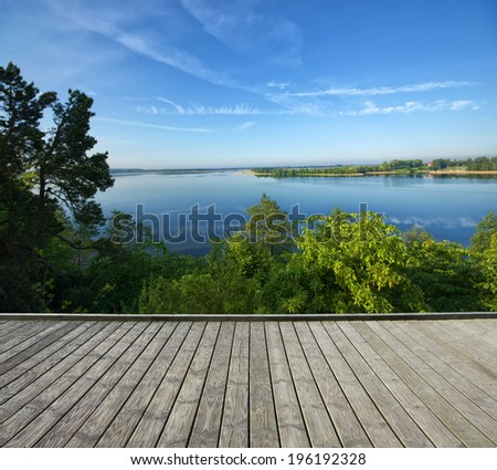 Empty wooden terrace with top view of beautiful lake in the background