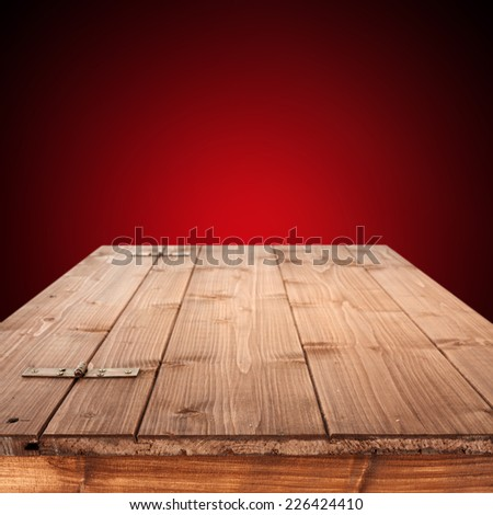 empty wooden top of box and red wall for you text