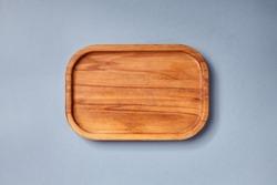 Empty wooden tray on textured dark blue table. Rectangular wooden dish top view. Kitchen minimal flat lay