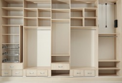Empty wooden wardrobe with shelves and drawers in dressing room