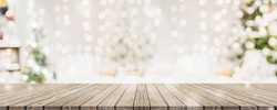 Empty woooden table top with abstract warm living room decor with christmas tree string light blur background with snow,Holiday backdrop,Mock up banner for display of advertise product