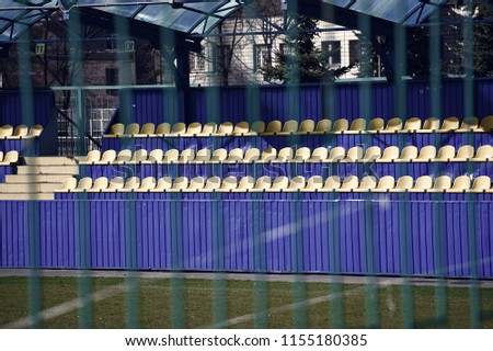 empty yellow and blue football stadium tribune behind fence of ukrainian educational training complex with green grass sunny outdoor for players team and match. sport and hobby #1155180385