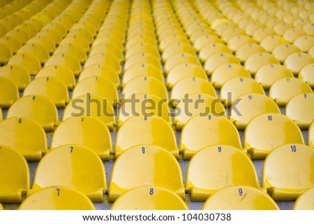 Empty yellow football stadium seats are creating a symetric view