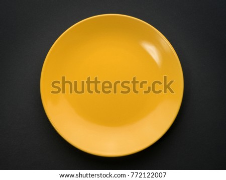 Empty yellow plate on black background. Top view