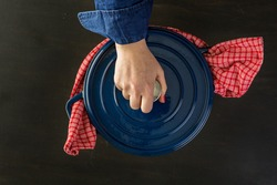 Enameled blue cast iron covered dutch oven on black wood table.