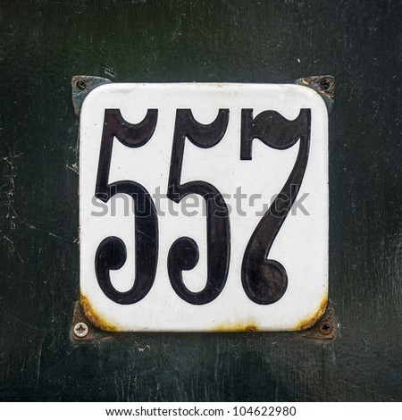 enameled house number five hundred and fifty-seven. Black lettering on a white background