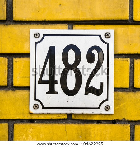 enameled house number four hundred and eighty-two on a yellow brick wall