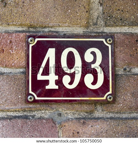 enameled house number four hundred and ninety-three. White lettering on dark red background - stock photo