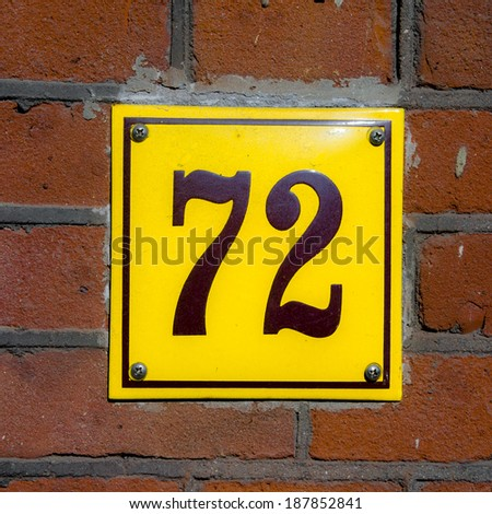 Enameled house number seventy two. Brown lettering on a yellow background.